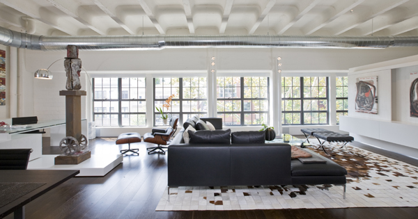 This contemporary Washington, DC loft, second home for an international power couple, features exposed ceilings and ductwork, classic furniture, and custom designed minimalist built-ins