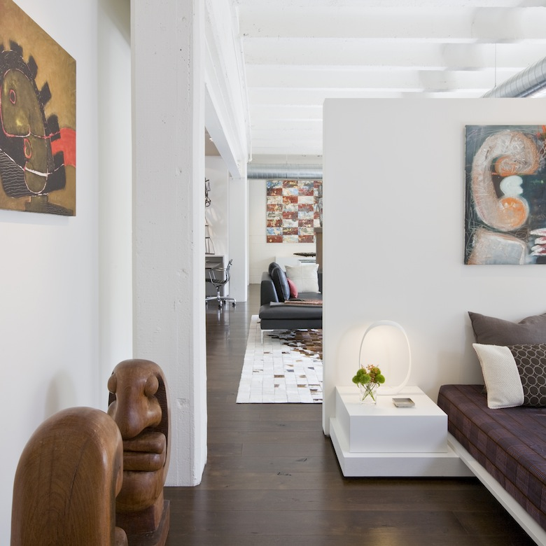 A short wall defines bedroom without chopping up the loft, second home for an international power couple, exposing the cement ceilings throughout the contemporary living space.