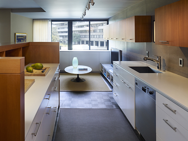 The tall island hides the mess contained in this open kitchen, completed by contrasting cabinetry