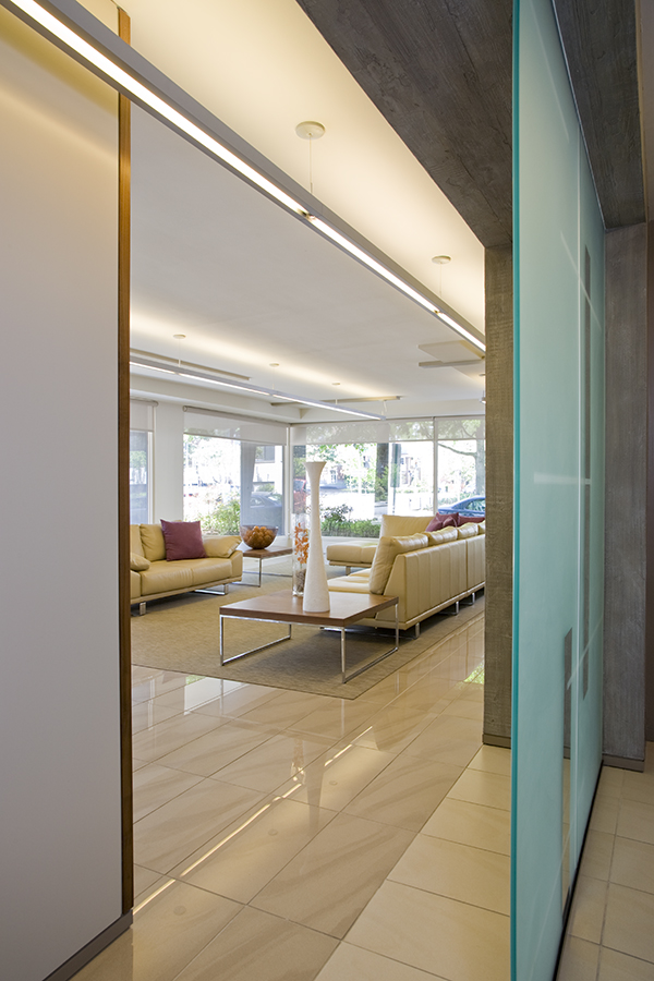 Cement paneling and frosted glass panels bathe this upscale modern condominium lobby in natural light