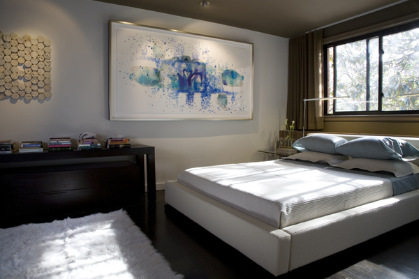 Modern artwork makes a bold statement in the bedroom of this condo by Washington, DC Architect and interior design firm Studio Santalla.