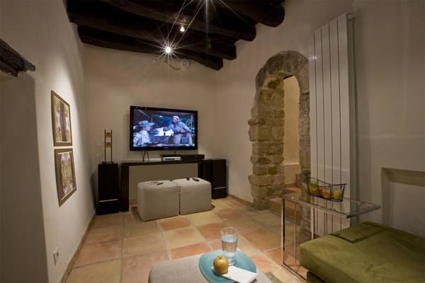 The media room of this 800 year old French town home renovation by Studio Santalla features exposed stone and roof beams.