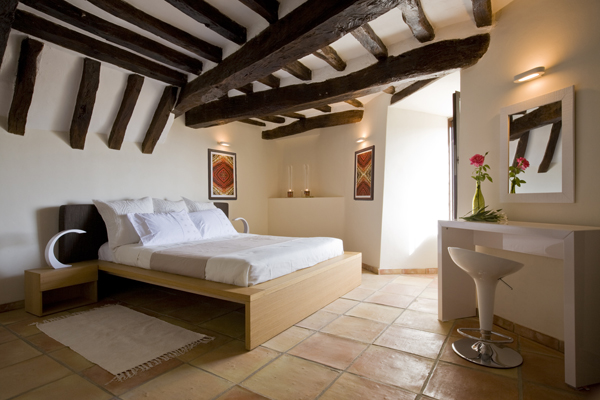 The roof beams in the bedroom of this 800 year old French home have been left exposed in the renovation by Washington, DC architect and interior design firm Studio Santalla