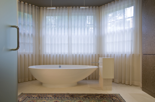 Elegant soaking tub in his and hers (jack and jill) master bathroom by Washington, DC Architect and Interior Design Firm Studio Santalla