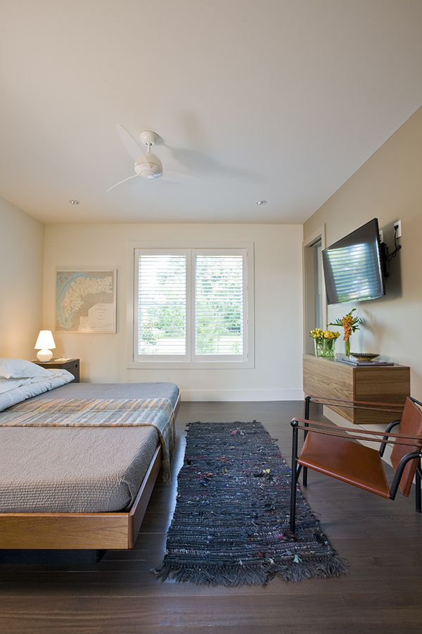 Clean and simple guest bedroom with floating dresser on the Eastern Shore by Washington, DC Architecture and Interior Design firm Studio Santalla