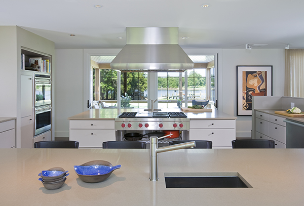 Massive, twin island kitchen in warm neutral colors with views of the Eastern Shore by Washington, DC Architecture and Interior Design firm Studio Santalla