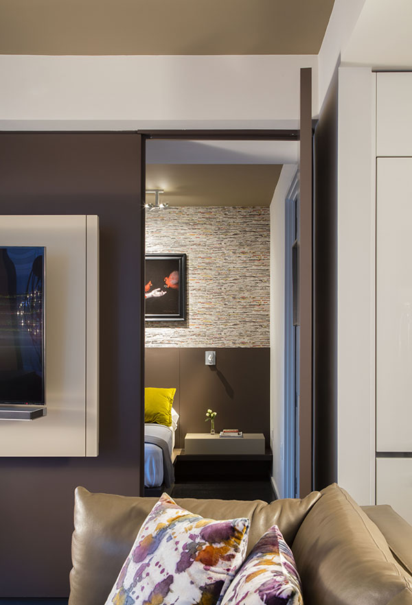 "The paneled wall includes an ""invisible"" door to the bedroom."