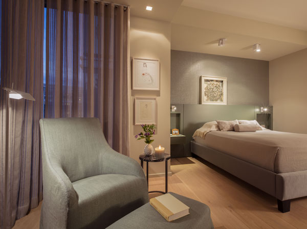 A custom headboard is paired with an upholstered bed and elegant furniture.