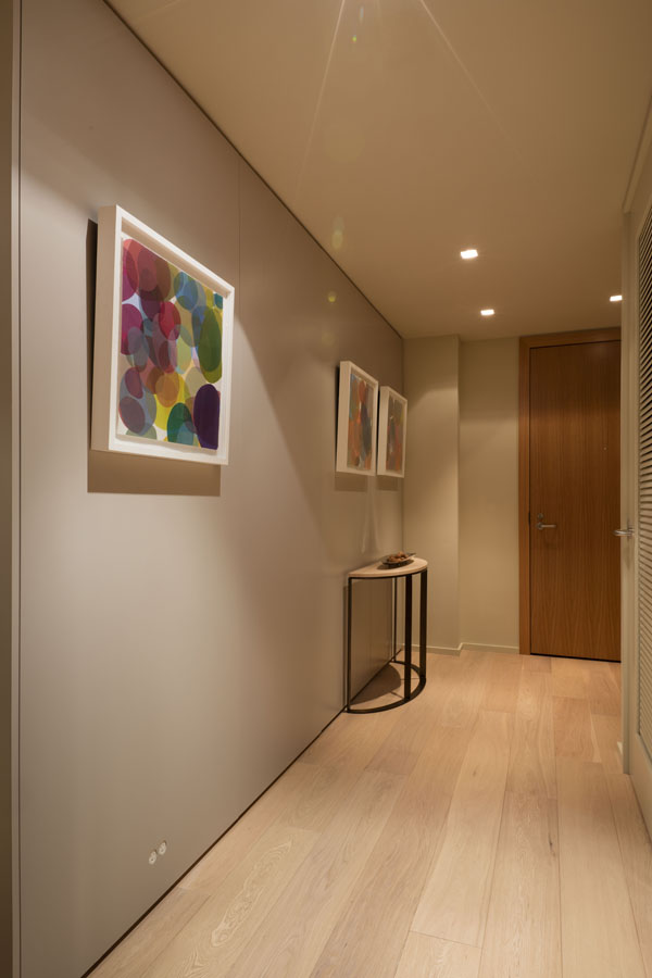 An unassuming entry way provides an elegant background for a sophisticated art collection, and hides the bedroom door.